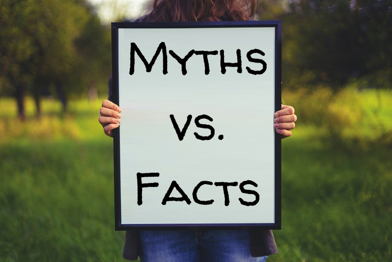 woman holding sign that says Facts vs. Myths